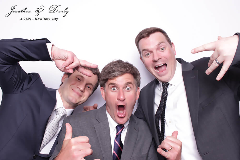 three friends pose with funny faces and hand signs in a Photo Booth in front of a bright white backdrop at the wedding of Jonathan and Darby