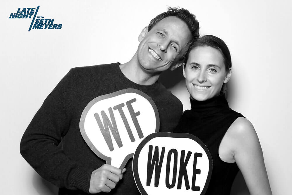 "Seth Meyers and wife Alexa Ashe pose in a black and white image with a photo booth sign prop that reads ""WTF"" and ""Woke"""
